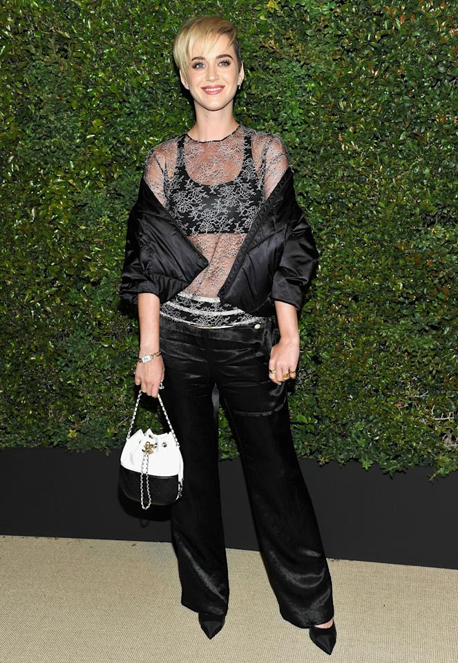 <p>in a black toile Chanel blouson, black satin Chanel pants, an Eres lace top, and Chanel shoes with a Chanel bag and Chanel Fine Jewelry rings, earrings, and a watch.</p>