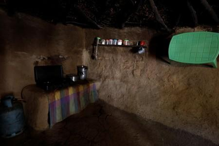 Cooking utensils sit on a side in a kitchen of a house built of mud and stone with roofed with wicker and thatch, in Oued al-Berber, Tunisia