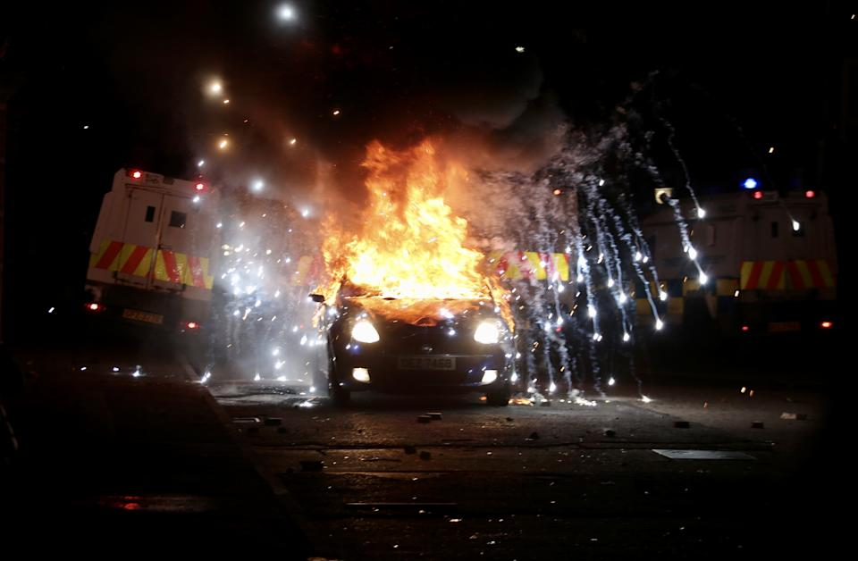 BELFAST, NORTHERN IRELAND - APRIL 09: Flames and smoke rise from car set a fire during protests as rioters hurled petrol bombs, fireworks and stones at police amid unrest since Wednesday, in Belfast, Northern Ireland on April 09, 2021. â¨The unrest started when some Sinn Fein members attended a crowded funeral on top of tensions caused by Brexit border arrangements, which brought checks on goods shipped between Northern Ireland and the rest of the UK. â¨Both loyalist and nationalist areas were involved in riots in west Belfast. (Photo by Hasan Esen/Anadolu Agency via Getty Images)