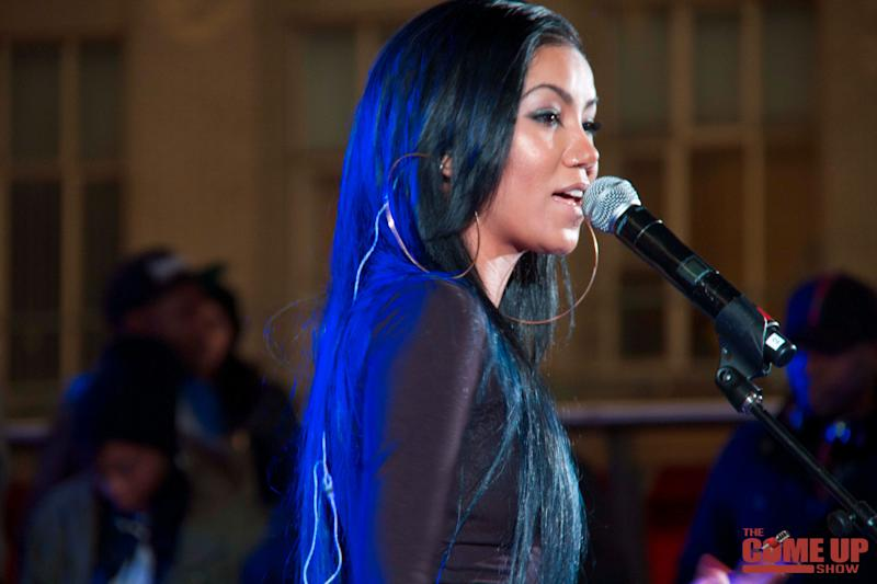 Jhene Aiko looks breath-taking in an all-black shiny outfit during a performance