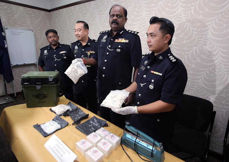 Assistant Superintendent Marafendi Marzuki (right) and Perak police narcotics chief Assistant Commissioner VR Ravi Chandran (2nd right) hold the drugs seized from a house in Taman Klebang Mutiara, Ipoh August 27, 2018. — Picture by Farhan Najib
