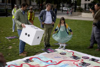 """Richard Ratcliffe, the husband of imprisoned British-Iranian Nazanin Zaghari-Ratcliffe, center, and their seven year old daughter Gabriella stand by a giant snakes and ladders board in Parliament Square, London, to show the """"ups and downs"""" of Zaghari-Ratcliffe's case to mark the 2,000 days she has been detained in Iran, Thursday, Sept. 23, 2021. Zaghari-Ratcliffe was originally sentenced to five years in prison after being convicted of plotting the overthrow of Iran's government, a charge that she, her supporters and rights groups deny. While employed at the Thomson Reuters Foundation, the charitable arm of the news agency, she was taken into custody at the Tehran airport in April 2016 as she was returning home to Britain after visiting family. (AP Photo/Matt Dunham)"""