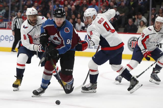 Colorado Avalanche right wing Mikko Rantanen, center, drives between Washington Capitals left wing Alex Ovechkin, left, and defenseman Dmitry Orlov in the first period of an NHL hockey game Thursday, Feb. 13, 2020, in Denver. (AP Photo/David Zalubowski)