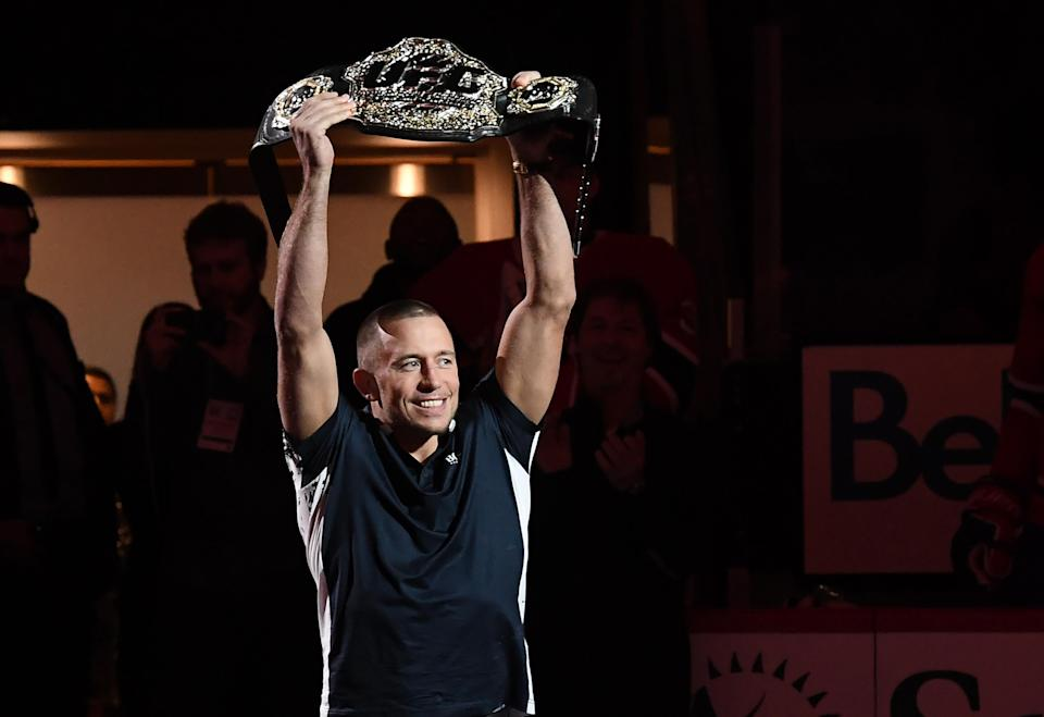 George St-Pierre holds up his middleweight title belt prior to an NHL game at the Bell Centre on Nov. 14, 2017 in Montreal. (Getty Images)