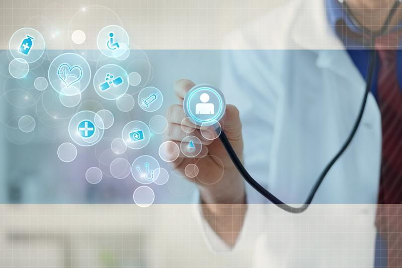 A doctor holding a stethoscope up to a digital image of a person, illustrating telehealth.