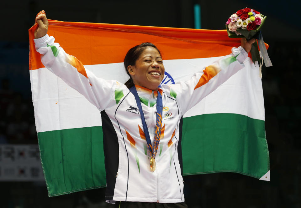 FILE - In this Wednesday, Oct. 1, 2014, file photo, India's M.C. Mary Kom holds the Indian national flag and celebrates her gold medal in the women's flyweight (48-51kg) final boxing match at the 17th Asian Games in Incheon, South Korea. Kom, whose inspirational life story spawned films and books, qualified for a third Olympics. (AP Photo/Kin Cheung, File)