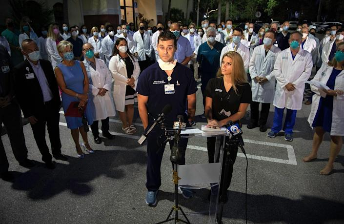 Emergency Room physicians Dr. Ethan Chapin and Dr. JT Snarski speak out as a group of doctors and administrators gathered in Palm Beach Gardens early Monday morning, August 23, 2021 to support vaccinations and the wearing of masks in their fight against COVID-19.  The entire physician staff of Palm Beach Gardens Medical Center was invited, as well as doctors from other area hospitals.