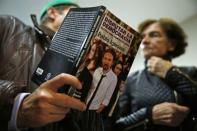 """A man talks about a book he is holding, written by Pablo Iglesias, Secretary General of the party """"Podemos"""" (We Can), to a woman at the end of their local assembly in Madrid's Salamanca district December 18, 2014. REUTERS/Susana Vera"""