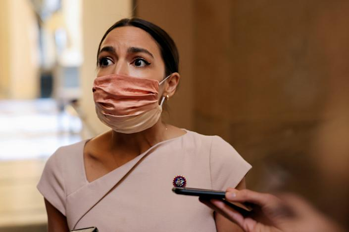 <p>Alexandria Ocasio-Cortez as she walks past reporters on Capitol Hill in Washington on 13 May, 2021.</p> (REUTERS)