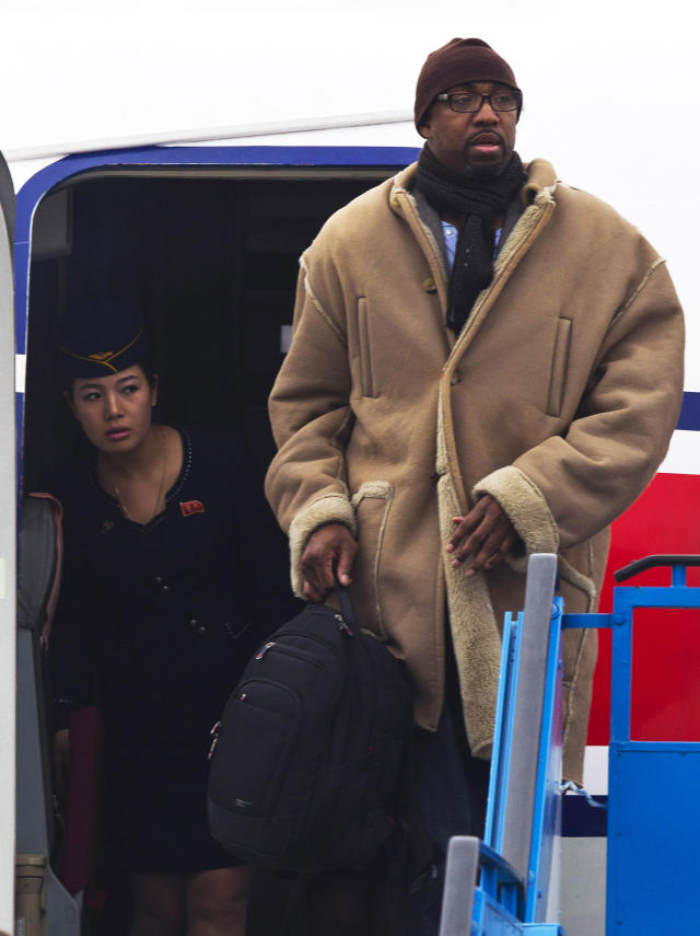 "A North Korean Air Koryo flight attendant peeks out from the aircraft door as former NBA basketball player Vin Baker arrives at the international airport in Pyongyang, North Korea Monday, Jan. 6, 2014. Dennis Rodman arrived in the North Korean with a squad of former basketball stars including Baker in what Rodman calls ""basketball diplomacy,"" although U.S. officials have criticized his efforts. (AP Photo/Kim Kwang Hyon)"