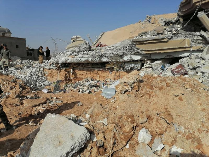 "Fighters from the Kataeb Hezbollah, or Hezbollah Brigades militia, inspect the destruction of their headquarters in the aftermath of a U.S. airstrike in Qaim, Iraq, Monday, Dec. 30, 2019. The Iranian-backed militia said Monday that the death toll from U.S. military strikes in Iraq and Syria against its fighters has risen to 25, vowing to exact revenge for the ""aggression of evil American ravens."" (AP Photo)"