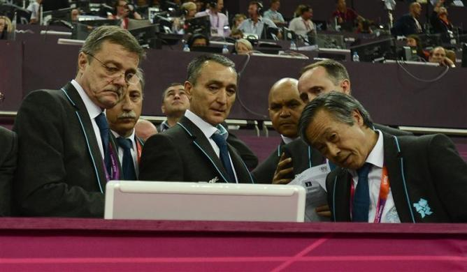 Human error caused the scoring error that kept Japan waiting for the silver medal in the Olympic gymnastics team event, and a robust review system quickly righted the wrong, a senior official said. Judges check the monitor after Japan's team complained at the men's gymnastics team final in the North Greenwich Arena during the London 2012 Olympic Games July 30, 2012.