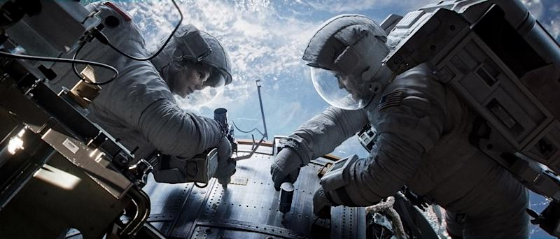 """This publicity photo released by Courtesy of Warner Bros. Pictures shows Sandra Bullock, left, as Dr. Ryan Stone and George Clooney as Matt Kowalsky in Warner Bros. Pictures' sci-fi thriller """"Gravity,"""" a Warner Bros. Pictures release. (AP Photo/Courtesy Warner Bros. Pictures)"""