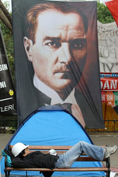 A protester relaxes on a bench as a portrait of Mustafa Kamal Ataturk, founder of the modern Turkey, is hanged in the background at the Gezi park of Taksim Square in Istanbul on Thursday, June 13, 2013. Turkey's government on Wednesday offered a first concrete gesture aimed at ending nearly two weeks of street protests, proposing a referendum on a development project in Istanbul that triggered demonstrations that have become the biggest challenge to Prime Minister Recep Tayyip Erdogan's 10-year tenure. (AP Photo/Thanassis Stavrakis)