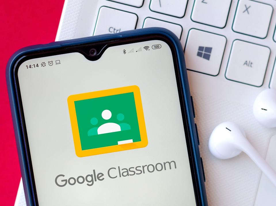 Google Classroom app on an Android phone resting on a Mac laptop