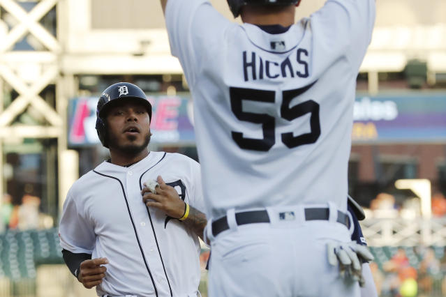 Detroit Tigers' John Hicks (55) waits on teammate Harold Castro as they both score on a single by Victor Reyes during the second inning of a baseball game against the Seattle Mariners, Wednesday, Aug. 14, 2019, in Detroit. (AP Photo/Carlos Osorio)