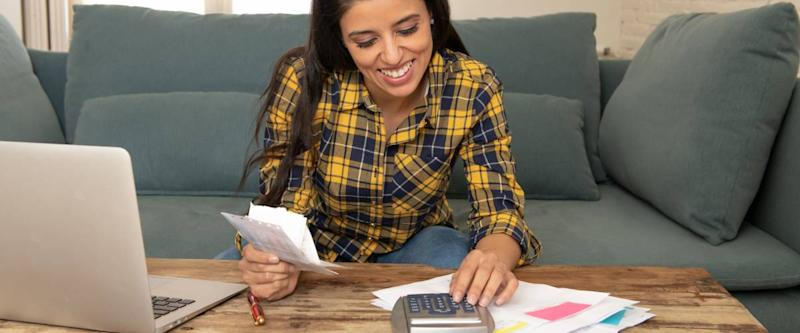 Happy attractive latin woman calculating home finances, accounting costs, charges, taxes, mortgage and paying bills at home using calculator and laptop looking cheerful and relax