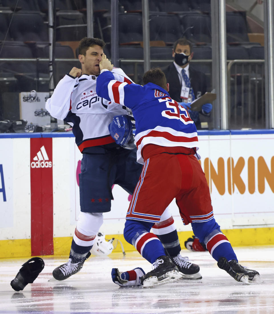 Washington Capitals' Garnet Hathaway (21) fights with New York Rangers' Phillip Di Giuseppe (33) during the first period of an NHL hockey game Wednesday, May 5, 2021, in New York. (Bruce Bennett/Pool Photo via AP)