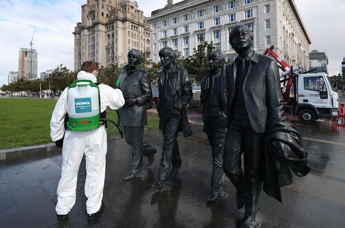 A worker spray cleans the Beatles statue in Liverpool. New coronavirus restrictions in Liverpool, Warrington, Hartlepool and Middlesbrough will come into force on Saturday morning at one minute past midnight, Downing Street has said.
