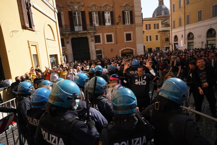 Demonstrators scuffle with Italian Policemen during a protest by Restaurant and shop owners outside the Lower Chamber in Rome, Tuesday, April 6, 2021. Demonstrators demanded to reopen their business and protested against restrictive measures by the Italian Government to cope with the surge of COVID-19 cases. (AP Photo/Andrew Medichini)