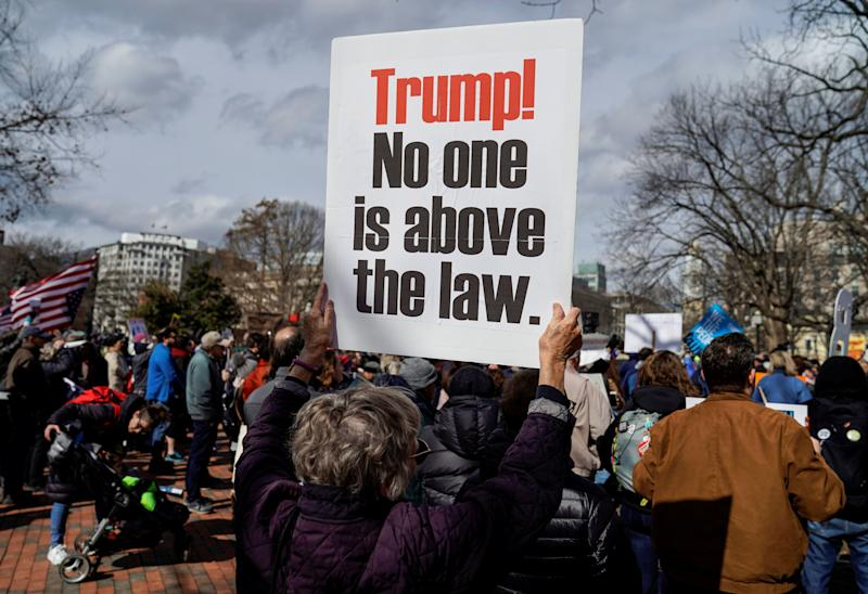 A woman holds a sign during a demonstration against U.S. President Donald Trump on President's Day near the White House in Washington, Feb. 18, 2019. (Photo: Joshua Roberts/Reuters)