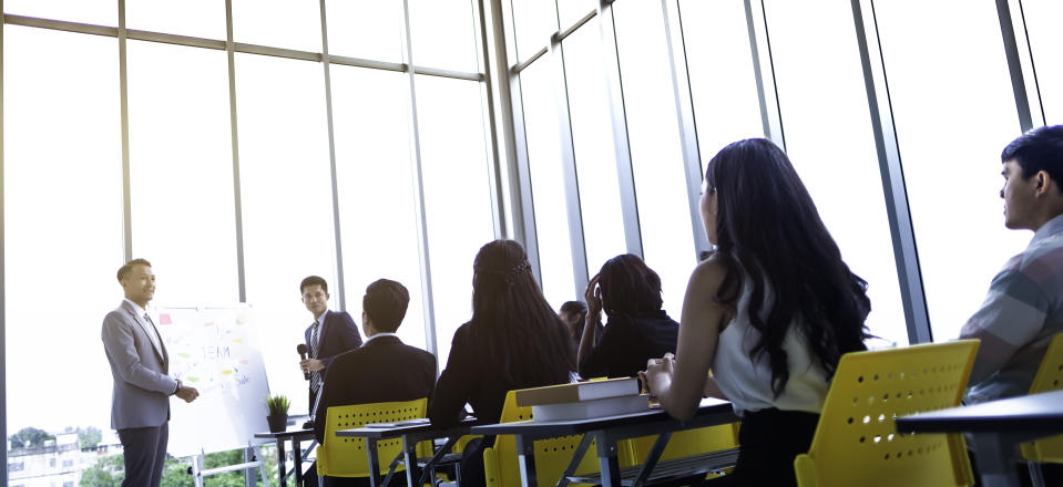 Group of attentive adult students with speaker giving a talk or trainer in classroom or seminar at business training to success of target.