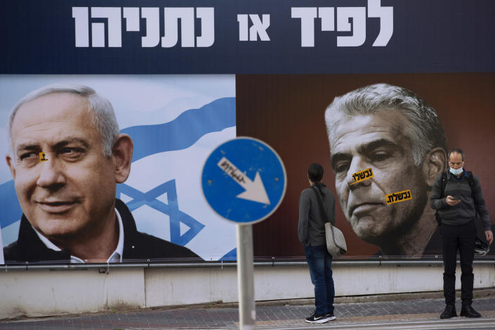 FILE - In this March 14, 2021 file photo, people stand in front of an election campaign billboard for the Likud party showing a portrait of its leader Prime Minister Benjamin Netanyahu, left, and opposition party leader Yair Lapid, in Ramat Gan, Israel. Israel's President Reuven Rivlin has tapped Lapid to form a new government, a step that could lead to the end of Netanyahu's lengthy rule. (AP Photo/Oded Balilty, File)