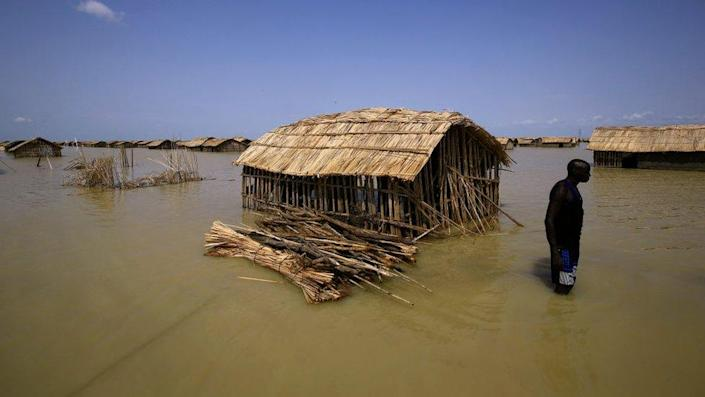 South Sudanese refugees try to repair their hut in flooded waters from the White Nile at a refugee camp which was inundated after heavy rain near in al-Qanaa in southern Sudan, on September 14, 2021.