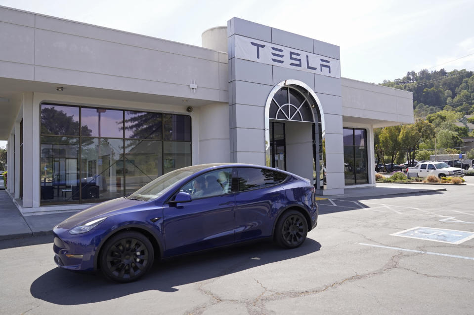 FILE - In this April 2, 2021 file photo two women in an electric car drive into a Tesla delivery location and service center in Corte Madera, Calif. California's Department of Motor Vehicles is reviewing whether Tesla is violating a state regulation by advertising its vehicles as being fully autonomous without meeting the legal definition of self-driving The department says Monday, May 17, 2021 that the regulation prohibits advertising vehicles for sale or lease as autonomous if the regulation isn't met. (AP Photo/Eric Risberg,File)