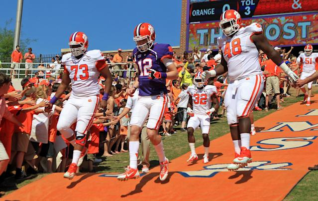 From left, Clemson's Joe Gore, Nick Schuessler and D.J. Reader run down The Hill at Memorial Stadium before the NCAA college football team's spring game Saturday, April 12, 2014, in Clemson, S.C. (AP Photo/Anderson Independent-Mail, Mark Crammer)