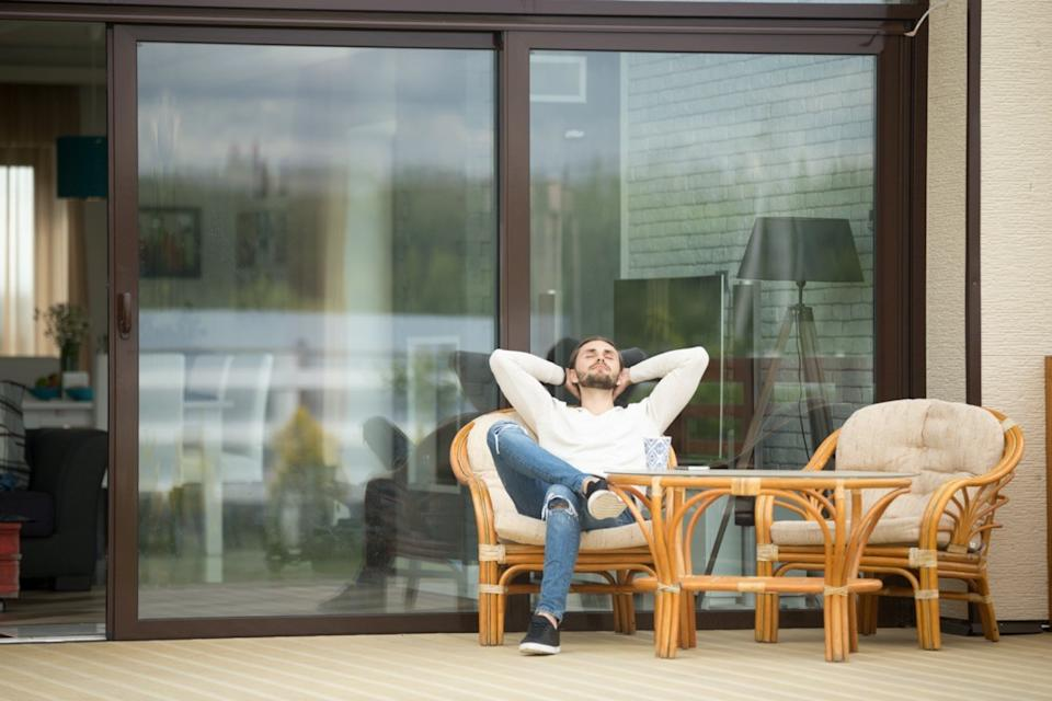 man relaxing sitting on terrace chair hands behind head