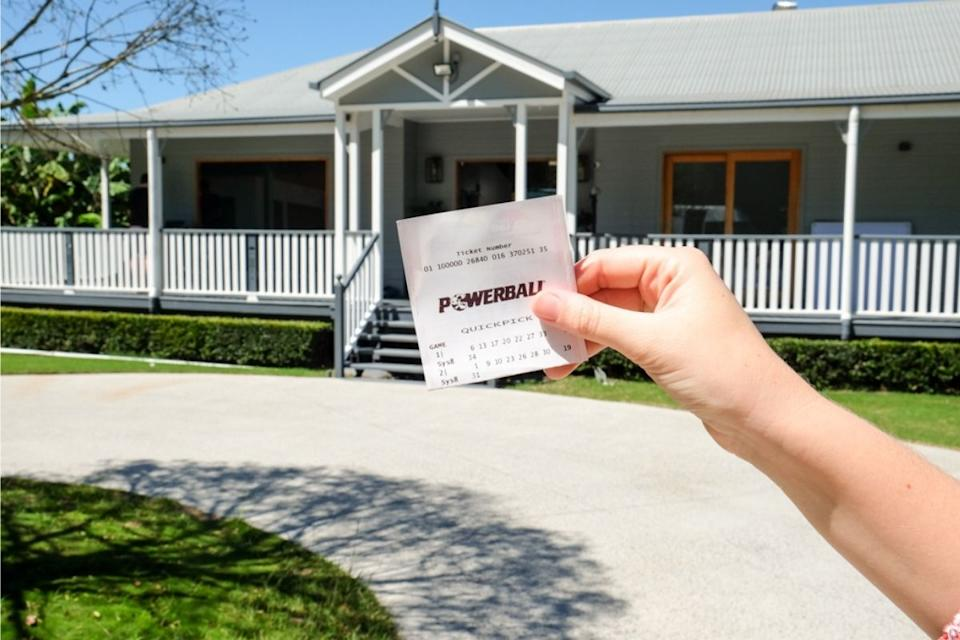 Hand holds a Powerball lottery ticket in front of dream house. Source: The Lott