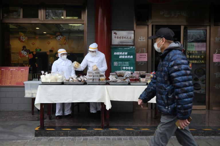 Restaurant workers wear protective clothing as they prepare food to sell on the street outside their restaurant in Beijing this week