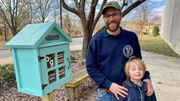 PHOTO: Sterling Marchand and his son pose in front of a little free food pantry. (Amber and Sterling Marchand/Be The Good Project)