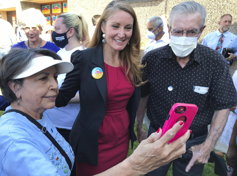 Democratic congressional candidate Melanie Stansbury, center, takes photos with supporters during a campaign rally in Albuquerque, New Mexico, on Thursday, May 27, 2021. She was joined by Doug Emhoff, the husband of Vice President Kamala Harris. The trip marked Emhoff's first on behalf of a candidate. (AP Photo/Susan Montoya Bryan)