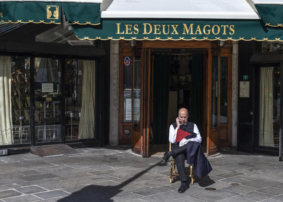 A man sits outside the closed famed Les Deux Magots cafe Sunday March 15, 2020 in Paris. French Prime Minister Edouard Philippe announced that France is shutting down all restaurants, cafes, cinemas and non-essential retail shops, starting Sunday, to combat the accelerated spread of the virus in the country. For most people, the new coronavirus causes only mild or moderate symptoms. For some it can cause more severe illness. (AP Photo/Rafael Yaghobzadeh)