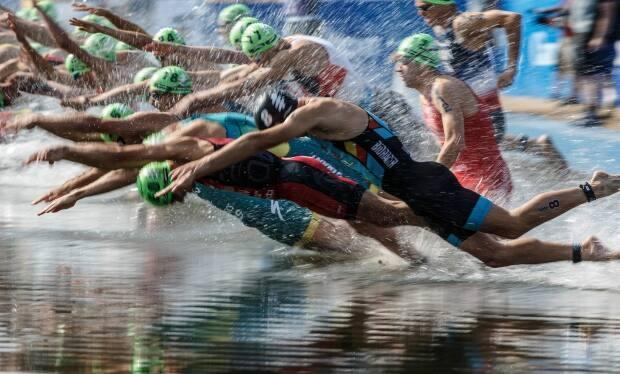 Athletes jump into the lake in Hawrelak Park during the Elite Men's race at the ITU World Triathlon Series in Edmonton in 2019.  (Jason Franson/The Canadian Press - image credit)