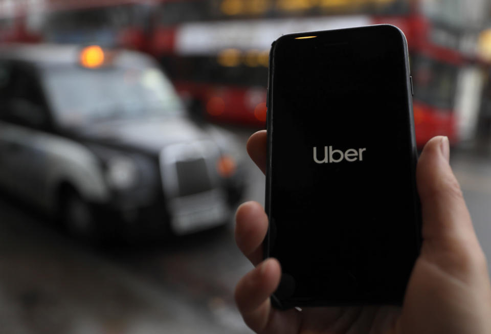 In this posed picture, the Uber app is opened on a mobile phone, backdropped by other transport services in London, Monday, Nov. 25, 2019.  London's transit authority on Monday refused to renew Uber's license to operate, with the ride-hailing company vowing to appeal the decision. (AP Photo/Kirsty Wigglesworth)