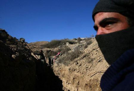 FILE PHOTO: A rebel fighter of Jaysh al-Islam digs a trench in Tal Farzat in the besieged rebel-held eastern Ghouta area of Damascus, Syria February 2, 2017. REUTERS/Bassam Khabieh