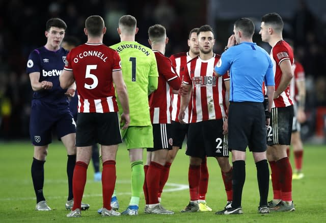 Players wait with referee Michael Oliver for the VAR decision (Martin Rickett/PA).