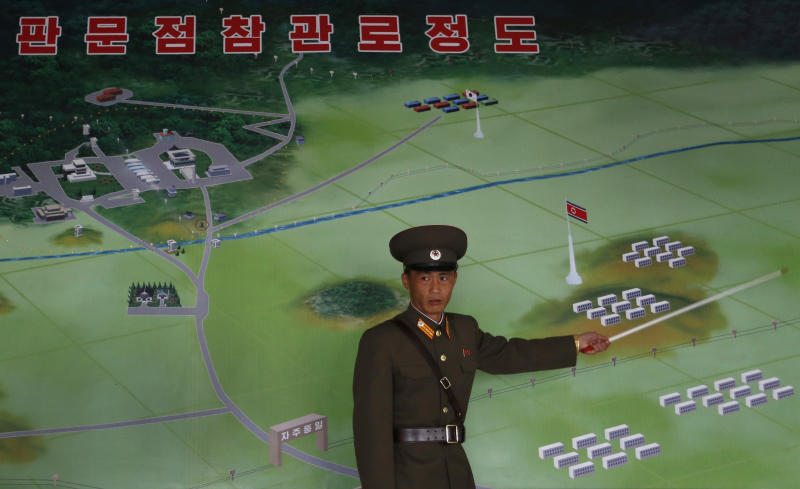"""A North Korean military officer points at a diagram of the Demilitarized Zone (DMZ) which separates the two Koreas at a building in Panmunjom, North Korea Monday, April 23, 2012. North Korea promised Monday to reduce South Korea's conservative government """"to ashes"""" in less than four minutes, in an unusually specific escalation of recent threats aimed at its southern rival. The statement by North Korea's military, carried by state media, comes amid rising tensions on the Korean peninsula. Both Koreas recently unveiled new missiles, and the North unsuccessfully launched a long-range rocket earlier this month. (AP Photo/Vincent Yu)"""