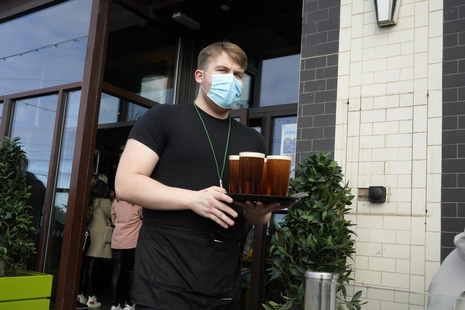 BLACKPOOL, ENGLAND - OCTOBER 16: A barman serves drinks at a Wetherspoon pub on the promenade on October 16, 2020 in Blackpool, England. The Lancashire region will go into Tier 3 of Covid-19 lockdown restrictions from 00.01 Saturday 17th October. (Photo by Christopher Furlong/Getty Images)