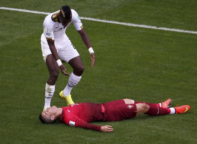 Ghana's John Boye (L) reacts after colliding with Portugal's Cristiano Ronaldo during their 2014 World Cup Group G soccer match at the Brasilia national stadium in Brasilia June 26, 2014. REUTERS/David Gray (BRAZIL - Tags: SOCCER SPORT WORLD CUP)