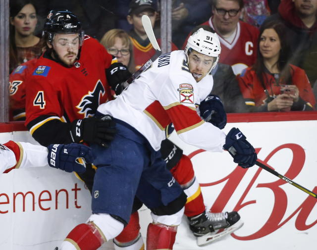 Florida Panthers' Juho Lammikko, right, of Finland, checks Calgary Flames' Rasmus Andersson, of Sweden, during an NHL hockey game in Calgary, Alberta, Friday, Jan. 11, 2019. (Jeff McIntosh/The Canadian Press via AP)
