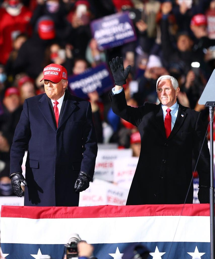 TRAVERSE CITY, MI – NOVEMBER 02: U.S. President Donald Trump (L) and U.S. Vice President Mike Pence (R) greet supporters at a rally on November 2, 2020 in Traverse City, Michigan. President Trump and former Vice President Democratic presidential nominee Joe Biden are making multiple stops in swing states ahead of the general election on November 3rd. (Photo by Rey Del Rio/Getty Images)