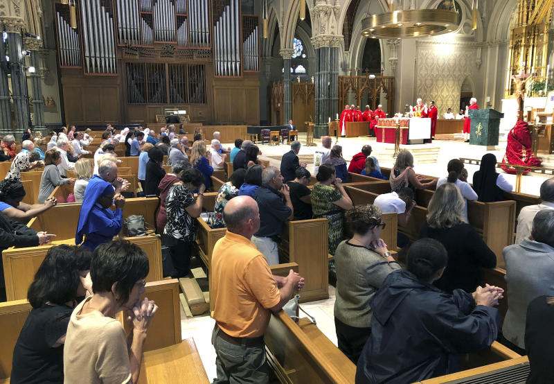 Parishioners kneel as Providence diocese Bishop Thomas Tobin, right begins Mass at the Cathedral of Saints Peter and Paul in Providence, R.I., Friday, Sept. 14, 2018. Tobin called for a day of prayer and penance he called for due to the sex abuse scandal in the Roman Catholic Church. (AP Photo/Jennifer McDermott)