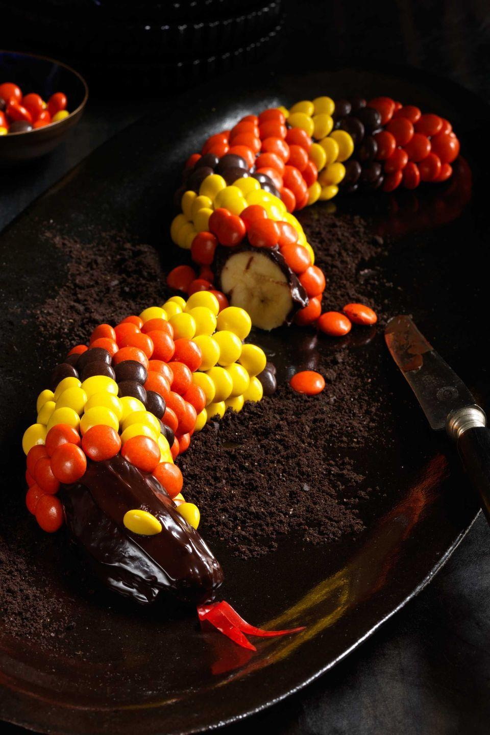 """<p>Peanut butter, chocolate, and bananas — what could be better? Rolling all those flavors together into a slithery sweet snake for Halloween, that's what.</p><p><strong><em><a href=""""https://www.womansday.com/food-recipes/food-drinks/recipes/a11984/peanut-chocolate-banana-snakes-recipe-123645/"""" rel=""""nofollow noopener"""" target=""""_blank"""" data-ylk=""""slk:Get the Peanut and Chocolate Banana Snakes recipe."""" class=""""link rapid-noclick-resp"""">Get the Peanut and Chocolate Banana Snakes recipe. </a></em></strong></p>"""