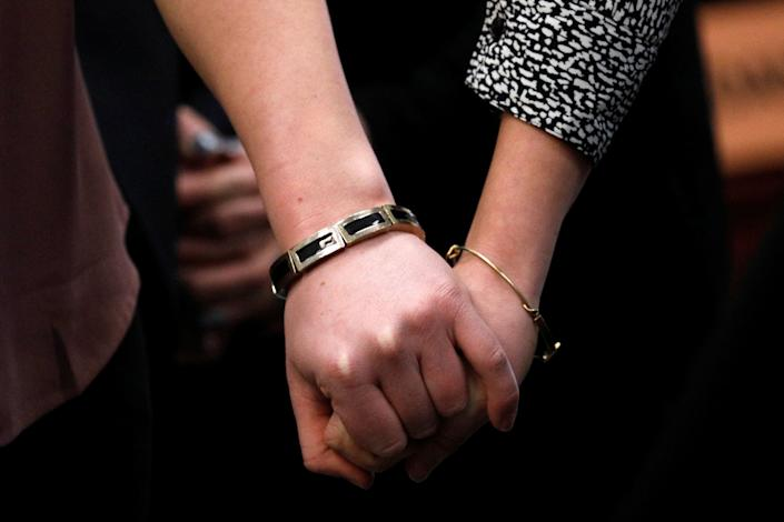 Victims and former gymnasts Maddie and Kara Johnson hold hands as they speak at the sentencing hearing. (Photo: Brendan McDermid/Reuters)