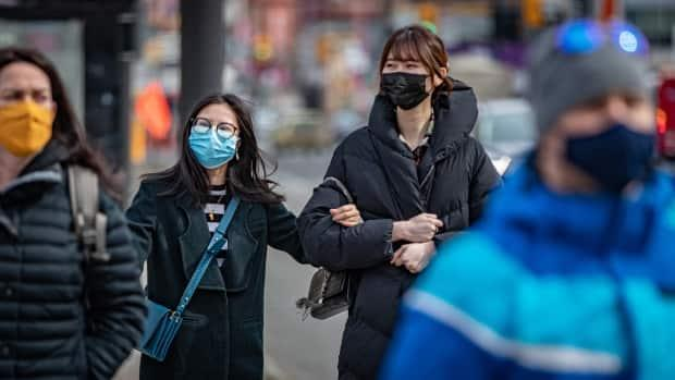 Pedestrians wear masks while walking along a busy street in downtown Ottawa on March 16, 2021.
