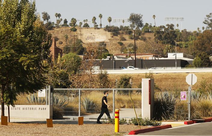 A man in a mask walks on the sidewalk in front of the gate to Los Angeles State Historic Park